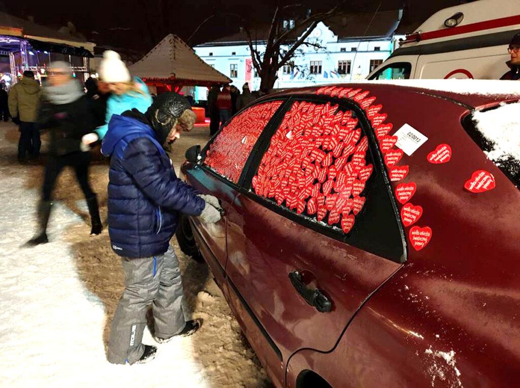 Tradycyjne już w Krośnie obklejanie samochodu WOŚP-owymi serduszkami